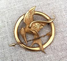 Quel oiseau est représenté sur la broche de Katniss ?
